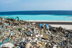 Descarga de lixo perto da praia perto do oceano completamente do fumo, da maca, de garrafas plásticas, de desperdícios e de lixo  imagens de stock royalty free