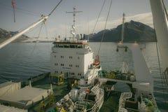 Descarga de pescados congelados a partir de un buque a otro buque en el mar Fotos de archivo libres de regalías