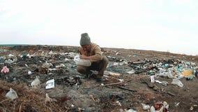 Descarga dos sem abrigo do homem em uns sem abrigo da operação de descarga que procuram o alimento entre o lixo pobreza social do filme