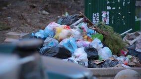 Descarga enorme do close-up de sacos de lixo com o desperdício que encontra-se na terra ao lado dos baldes do lixo na jarda resid video estoque