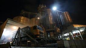 Descargando los camiones del grano en el elevador en la elevación del descargador hidráulico de la plataforma en la noche Transbo almacen de video