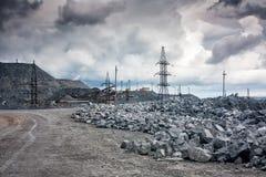 Descargas de piedra, líneas eléctricas y máquinas del machacamiento en una mina en tiempo nublado fotografía de archivo