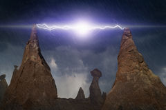 Descargas de relâmpago poderosas entre picos de duas rochas na obscuridade Imagem de Stock Royalty Free