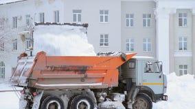 Descargas del cubo del excavador de la nieve en el camión almacen de metraje de vídeo