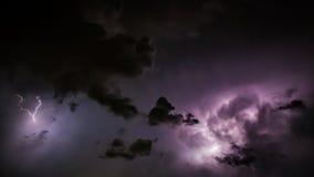 Descargas do parafuso de relâmpago em nuvens de tempestade roxas na noite Imagem de Stock