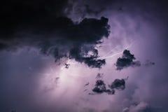 Descargas do parafuso de relâmpago em nuvens de tempestade roxas no fim da noite Fotografia de Stock