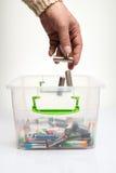 Descargue las baterías que se reciclarán, mano que lanza batteri del AA Fotos de archivo libres de regalías