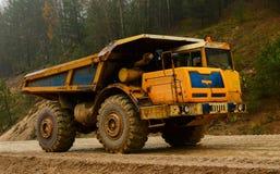 Descarregador diesel amarelo grande da pedreira no trabalho Caminhão de mineração pesado que transporta a areia e a argila imagens de stock