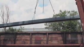Descarregamento da tubulação do perfil por um guindaste de pórtico de um carro de frete, metal das cargas em um armazém, um grand video estoque