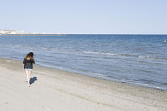 Descarte que camina de la mujer joven por una playa Foto de archivo