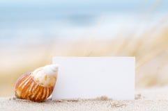 Descasque y una tarjeta en blanco en la playa Foto de archivo