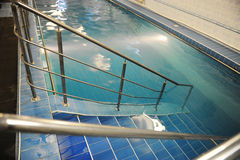 Descend the stairs in a blue pool. Pure clear water Royalty Free Stock Photography