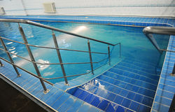 Descend the stairs in a blue pool. Pure clear water Royalty Free Stock Image
