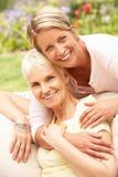 Descendant aîné de femme et d'adulte détendant dans le jardin Photo libre de droits