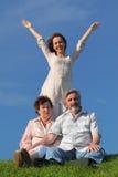 Descendant avec les mains distantes, parents s'asseyant sur la pelouse Image libre de droits