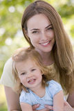 Descendant de fixation de mère souriant à l'extérieur Image libre de droits