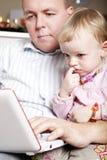 Descendant de père et de chéri sur l'ordinateur portatif photos stock