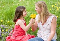 Descendant donnant des fleurs de mère Photo stock