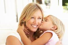 Descendant donnant le baiser de mère détendant sur le sofa Photo libre de droits