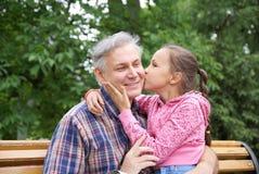 Descendant embrassant son père Photographie stock