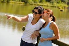 Descendant et mère détendant sur le pilier de lac Photographie stock