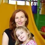 Descendant et mère ensemble dans la glissière de cour de jeu Images stock