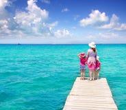Descendants et mère dans la jetée sur la plage tropicale Images libres de droits
