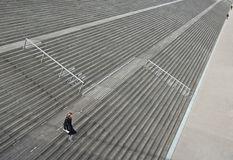 Descending. Woman holding document descending vast flight of stairs near the Paris Bibliotheque with tiny distant figures providing perspective and scale Royalty Free Stock Images