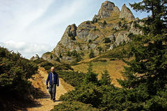 Descending from Ciucas mountains. Young man descending from Ciucas mountains in Romania on a beautiful spring day Royalty Free Stock Image