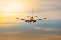 Descending commercial airplane in sunset with cloud Royalty Free Stock Photography
