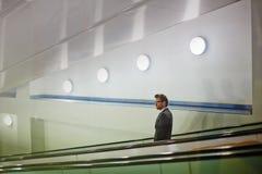 Descending on escalator. Young businessman standing on descending escalator Stock Image