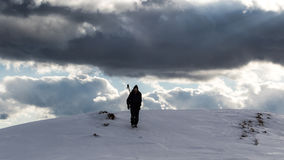 Man descending from the mountain through deep snow with a huge storm on the sky Royalty Free Stock Photography