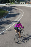 Descending by road cycle in a curve. A woman on the descent by road bike in a curve Royalty Free Stock Photos