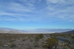 Descending Road into Death Valley California. Mountain Range sagebrush open sky Royalty Free Stock Photo