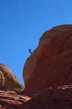 Descending rock climber. A side view of a rockclimber descending from a climb Royalty Free Stock Image