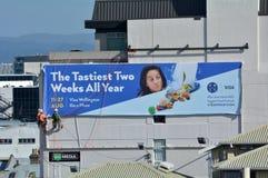 Descendre en rappel des travailleurs accrochant l'affiche géante de la publicité sur un bâtiment Images libres de droits
