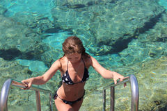 She descends into the clear water of the Mediterranean Sea Royalty Free Stock Photo