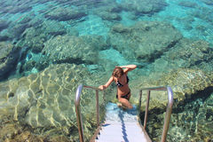 She descends into the clear water of the Mediterranean Sea Stock Images