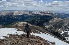 Descenso abajo de pico de montaña nevoso Foto de archivo