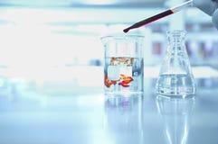Descenso anaranjado en el cubilete en laboratorio de ciencia Fotografía de archivo