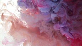 Descenso de la tinta del color en agua extensión azul claro, ciánica, roja, violeta del color almacen de metraje de vídeo