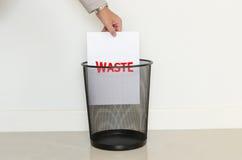 Descenso del hombre de negocios un papel inútil adentro a la basura Imagen de archivo libre de regalías