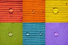 Descenso macro del agua de la composición en un paño coloreado Imagen de archivo