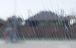 Descenso natural del agua sobre el vidrio fuera de la ventana, fondo de las casas Fotografía de archivo libre de regalías