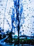 Descensos coloridos azules del agua sobre el vidrio Fotografía de archivo
