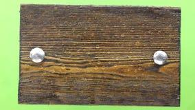 Descensos de la caída del agua en un tablero de madera oscuro con los pernos del hierro Aislado metrajes