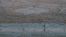 Descensos de la caída de la lluvia al pavimento que forma un charco Lapso de tiempo metrajes