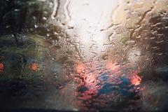 Descensos de la llovizna de la lluvia en el parabrisas de cristal en la tarde calle foto de archivo libre de regalías