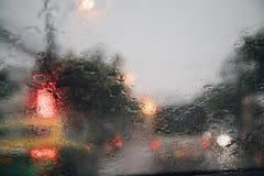 Descensos de la llovizna de la lluvia en el parabrisas de cristal en la tarde calle fotografía de archivo