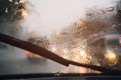 Descensos de la llovizna de la lluvia en el parabrisas de cristal en la tarde Calle en las fuertes lluvias foto de archivo libre de regalías